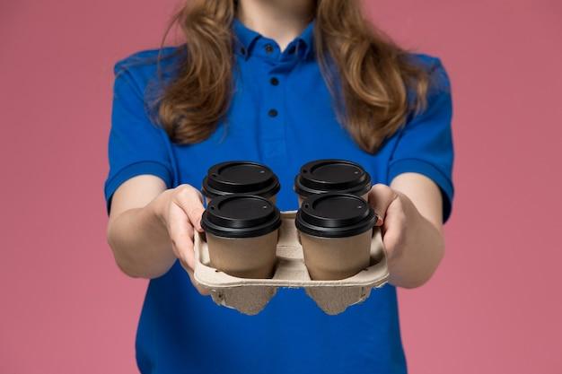 ピンクのデスクサービス制服会社の労働者に茶色の配達コーヒーカップを提供する青い制服の正面のクローズビュー女性宅配便