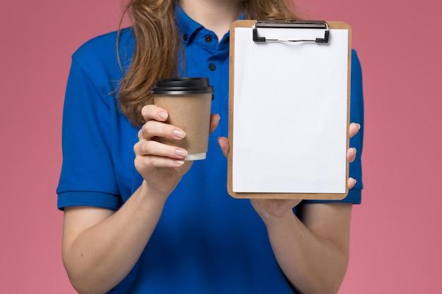 Крупным планом вид спереди женщина-курьер в синей форме, держащая коричневую кофейную чашку с блокнотом на светло-розовом столе, служба доставки униформы