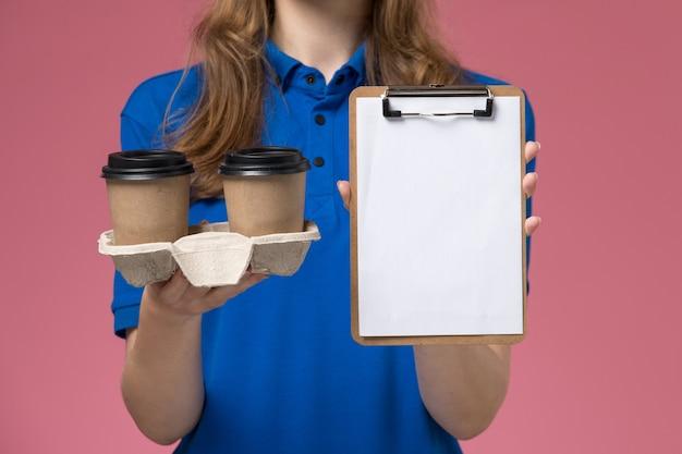 ピンクのデスクサービス制服会社の仕事で茶色の配達コーヒーカップとメモ帳を保持している青い制服の正面のクローズビュー女性宅配便