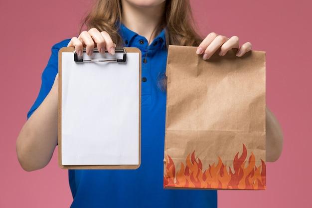 ライトピンクのデスクジョブワーカーサービスユニフォーム会社でメモ帳と食品パッケージを保持している青い制服の正面のクローズビュー女性宅配便