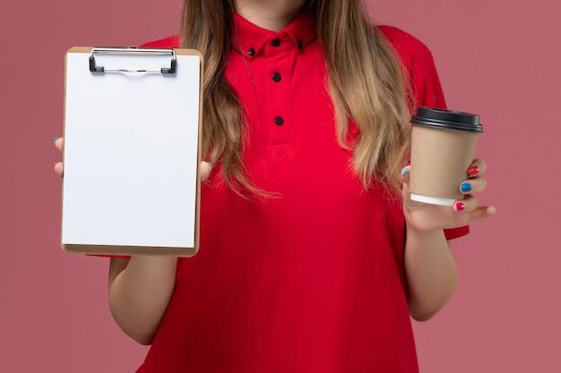 빨간색 유니폼과 케이프 밝은 분홍색 배경 서비스 작업 배달 유니폼에 메모장 배달 커피 컵을 들고 전면 닫기보기 여성 택배