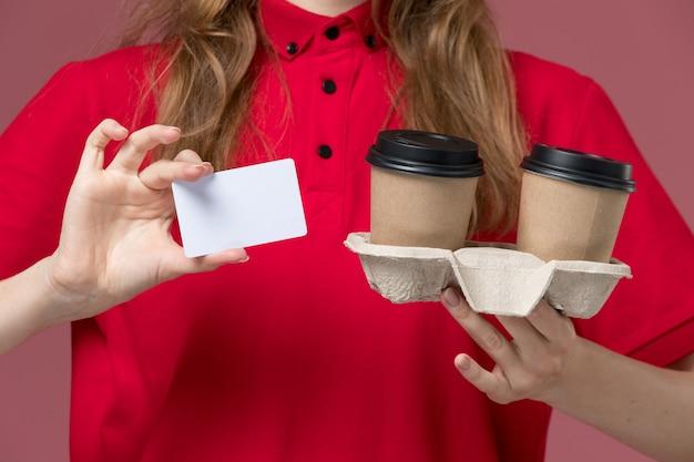 淡いピンクのカードと配達コーヒーカップを保持している赤い制服を着た正面の女性の宅配便、仕事の制服サービスワーカーの配達