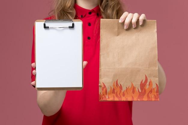 淡いピンクのメモ帳と食品パッケージを保持している赤い制服を着た正面の女性の宅配便、仕事の制服のサービスワーカーの配達