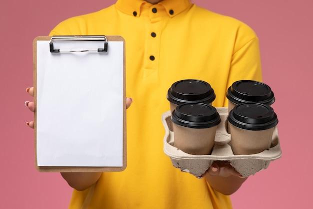 Вид спереди крупным планом женщина-курьер в желтой униформе с желтым плащом держит пластиковые кофейные чашки и блокнот на розовом фоне.
