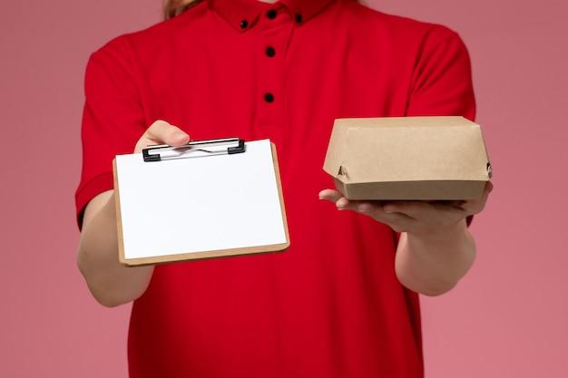 Corriere femminile di vista ravvicinata frontale in uniforme rossa e mantello che tiene un piccolo pacchetto di cibo per la consegna con il blocco note sulla parete rosa, consegna uniforme di servizio