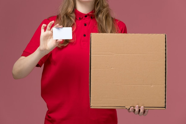 Front close view female courier in red uniform holding food box and white card on the pink, uniform service