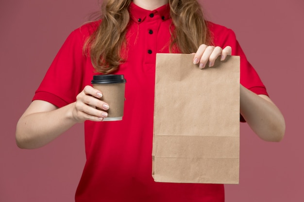 Front close view female courier in red uniform holding food package and coffee cup on pink, uniform service delivery job worker