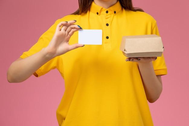 Corriere femmina vista frontale ravvicinata in uniforme gialla e mantello che tiene piccolo pacchetto di cibo per la consegna e carta sul muro rosa chiaro, lavoro di società di consegna uniforme di servizio