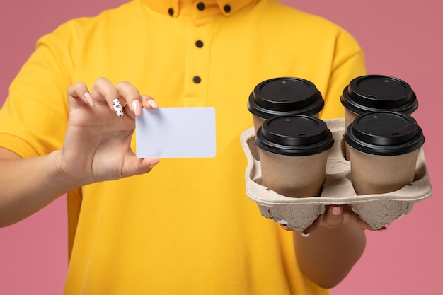 Front close view female courier in yellow uniform yellow cape holding coffee cups witj white card on pink background uniform delivery work color job