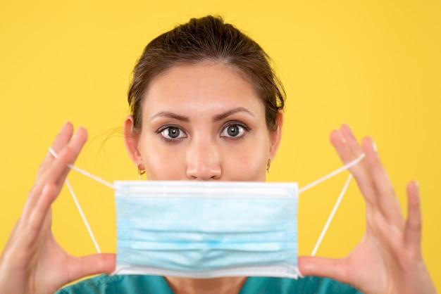 黄色の背景に滅菌マスクを保持している正面のクローズビュー女性医師