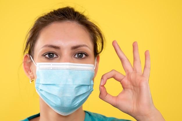 Вид спереди крупным планом женщина-врач в стерильной маске на желтом фоне