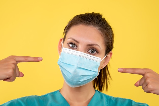 Front close view female doctor in sterile mask on a yellow background