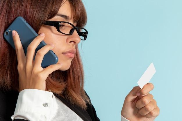 Фронт крупным планом женский офисный работник в строгом костюме разговаривает по телефону на синей поверхности