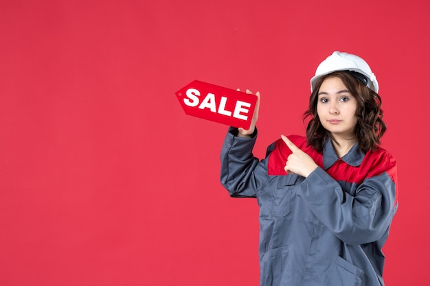 Front close view of female worker in uniform wearing hard hat and pointing sale icon on isolated red wall