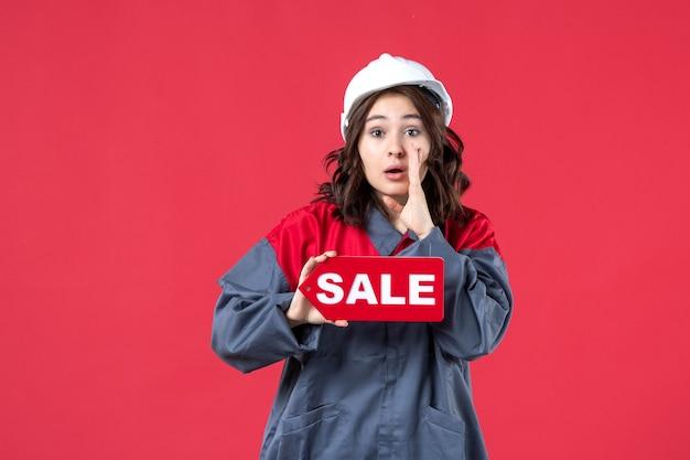 Vista frontale ravvicinata della lavoratrice in uniforme che indossa elmetto che mostra l'icona di vendita e chiama qualcuno sulla parete rossa isolata