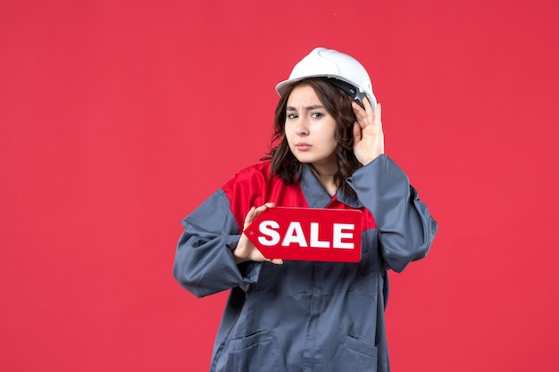 Front close view of female worker in uniform wearing hard hat showing sale icon and listening to the last gossiping on isolated red wall