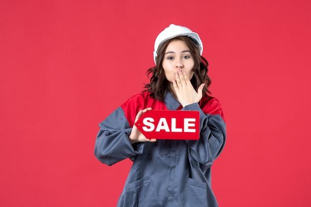 Vista frontale ravvicinata della lavoratrice in uniforme che indossa elmetto che mostra l'icona di vendita e che fa gesto di bacio sulla parete rossa isolata