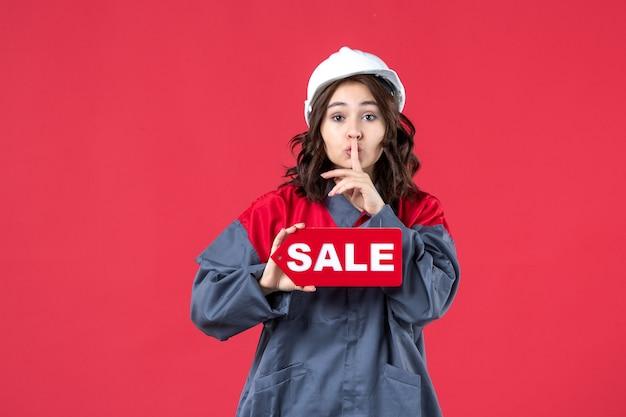 Vista frontale ravvicinata della lavoratrice in uniforme che indossa elmetto che mostra l'icona di vendita e che fa gesto di silenzio sulla parete rossa isolata