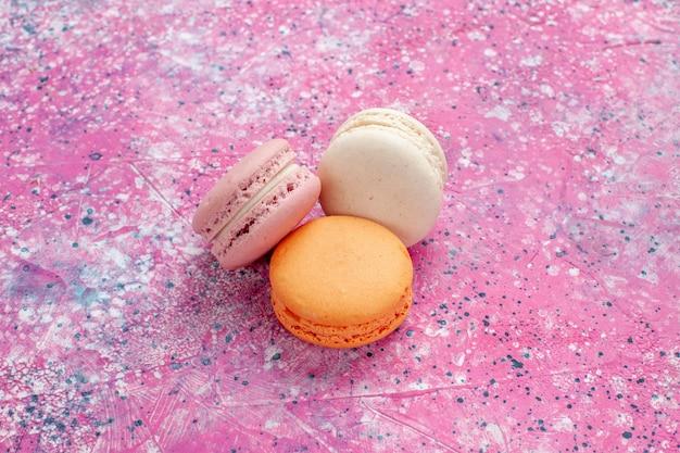 Vista ravvicinata anteriore francese macarons deliziose torte sulla scrivania rosa