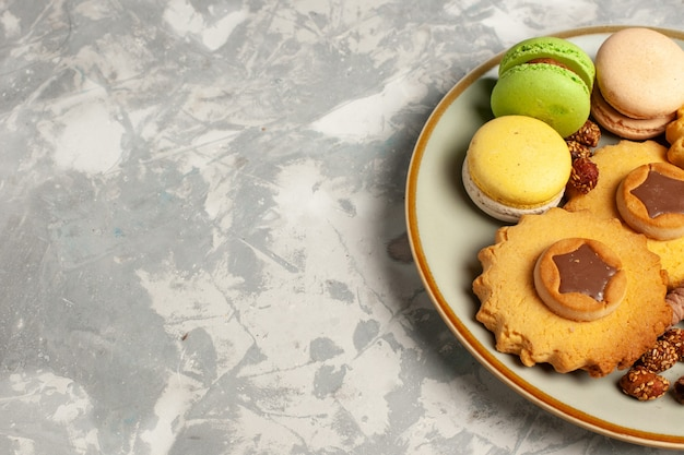 Macarons francesi di vista ravvicinata anteriore con torte e biscotti sulla superficie bianca