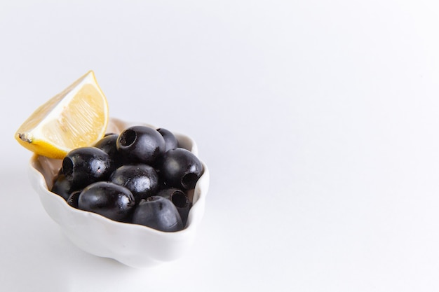 正面の拡大図白い表面にレモンスライスが付いた新鮮なブラックオリーブカラー写真食品植物油