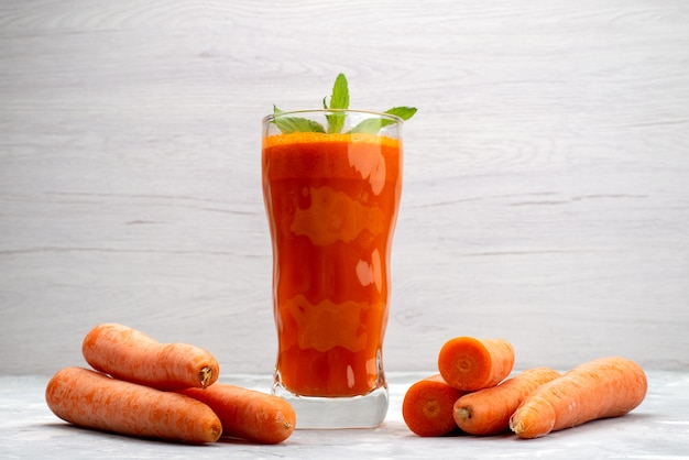 Front close view fresh carrot juice inside long glass with leaf and along with fresh carrots vegetable