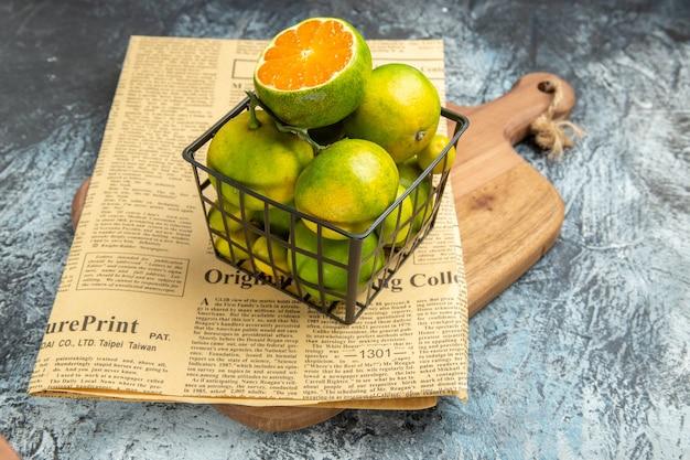 Vista frontale ravvicinata di agrumi freschi in un cesto di giornale su tagliere di legno su tavolo grigio