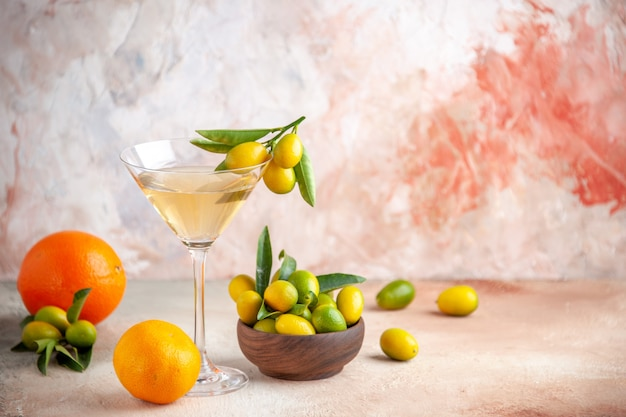 Front close view of fresh citrus fruits and wine in glass goblet on colorful surface