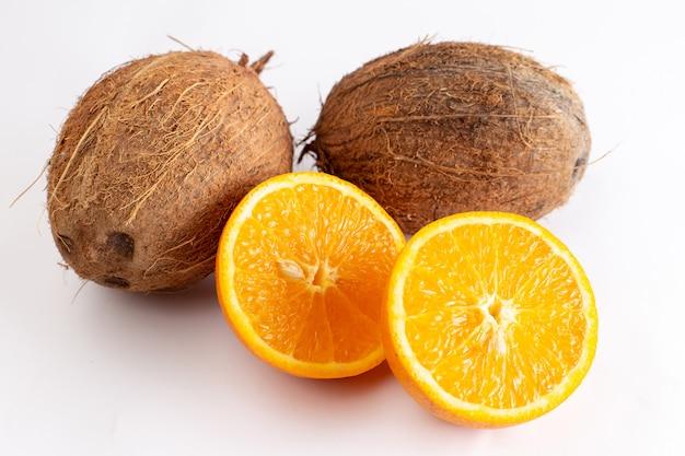 Noci di cocco fresche di vista vicina della parte anteriore insieme all'arancia affettata sulla superficie bianca