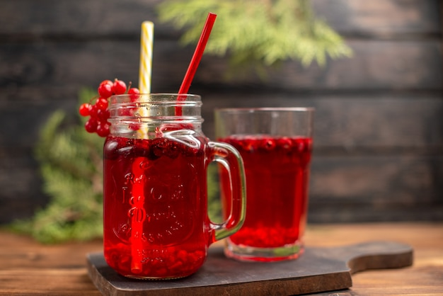 Front close view of fresh currant juice in a glass and a cup served with tube on a wooden cutting board on a brown table