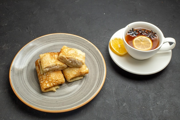 Front close view of fresh delicious pancakes on a white plate and a cup of black tea on dark background