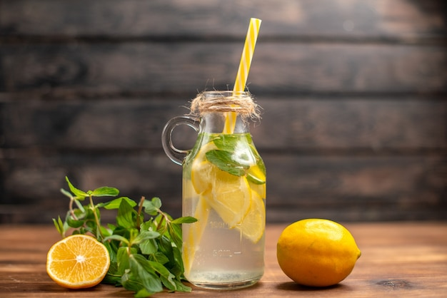 Front close view of fresh detox water served with tube mint and orange on a brown background