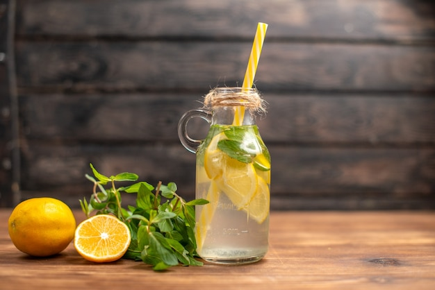 Front close view of fresh detox water served with tube mint and orange on the right side on a brown background