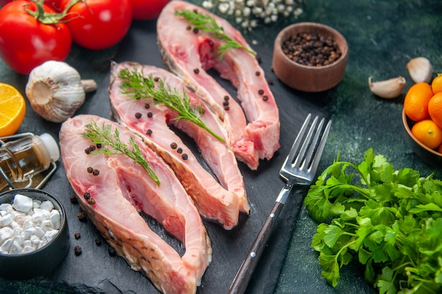 Vista frontale ravvicinata fette di pesce fresco con pomodori rossi e verdure sulla superficie scura insalata di frutti di mare pasto carne cruda acqua foto cena colore
