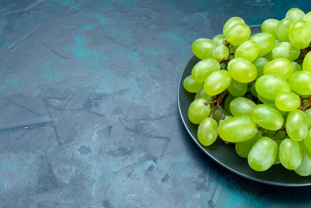 Front close view fresh green grapes juicy and mellow fruits on light-blue desk.