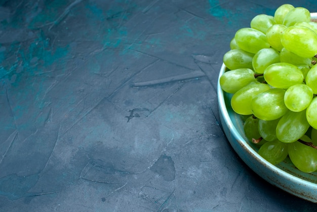 Front close view fresh green grapes mellow and juicy fruits inside plate on the dark-blue desk.