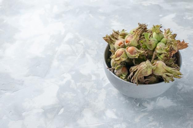 白い机の上の小さな鍋の中の新鮮なヘーゼルナッツを正面から見るナッツヘーゼルナッツスナックの木の植物