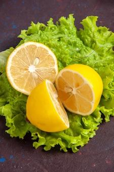 暗いスペースにグリーン サラダを添えた新鮮なレモン スライスを正面から見た図