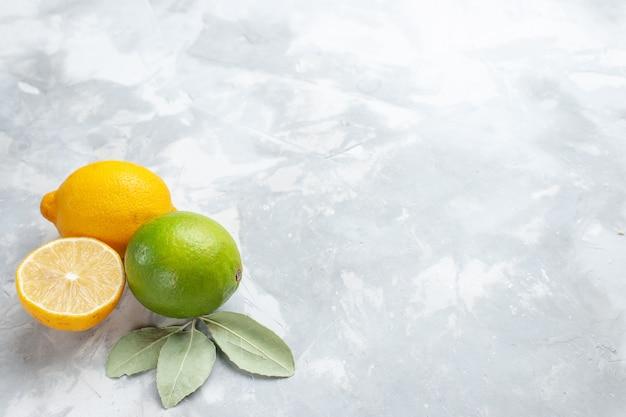 Limoni freschi di vista ravvicinata anteriore succosi e aspri sugli agrumi tropicali della frutta esotica dello scrittorio bianco