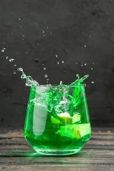 Vista frontale ravvicinata del delizioso succo naturale fresco in un bicchiere su sfondo nero