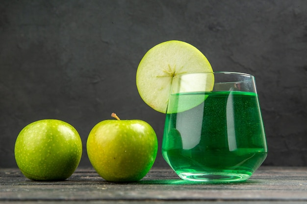 Vista frontale ravvicinata di un delizioso succo naturale fresco in un bicchiere e mele verdi su sfondo nero