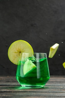 Front close view of fresh natural delicious juice in a glass served with apple limes on black background