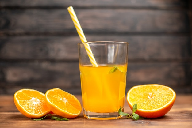 Front close view of fresh orange juice in a glass served with tube mint and orange limes on a wooden table