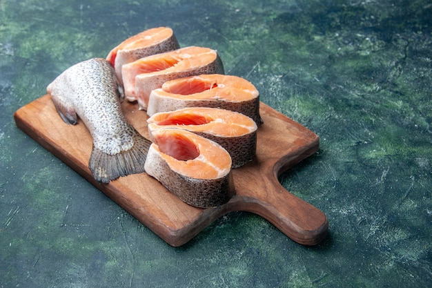 Front close view of fresh raw fishes on brown wooden cutting board on dark mix colors table with free space
