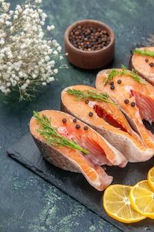 Vista ravvicinata frontale di fette di limone e pepe verdi di pesce crudo fresco sul vassoio di colore scuro sulla tabella dei colori della miscela