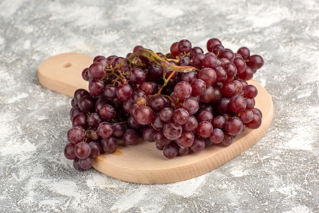 Front close view fresh red grapes mellow and juicy fruits on light-white surface