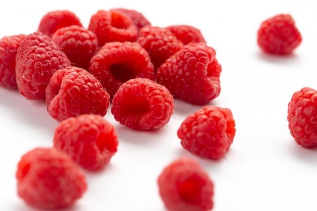 Спереди закрыть вид свежей красной малины, мягкие и кислые по всей белой поверхности