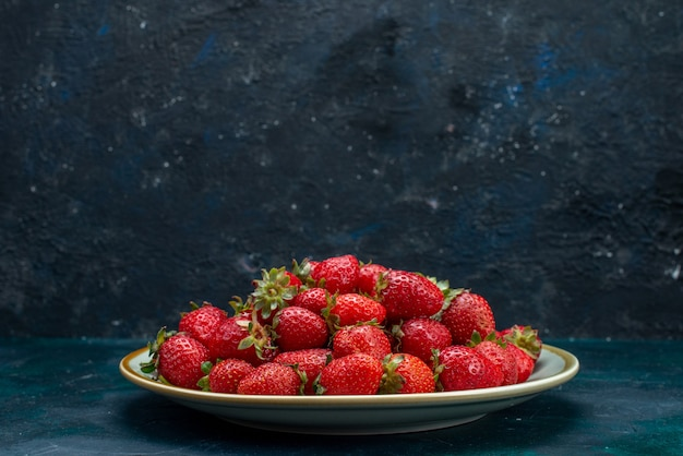 Front close view fresh red strawberries mellow fruits berries inside plate on the dark-blue background berry fruit mellow summer