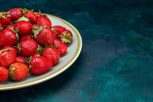 Vista ravvicinata frontale fragole rosse fresche frutti di bosco bacche all'interno della piastra sullo sfondo blu scuro frutti di bosco mellow summer