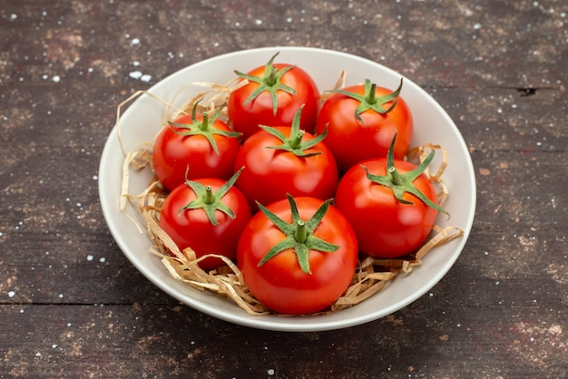 Front close view fresh red tomatoes inside white plate on the wooden brown background vegetable fruit color